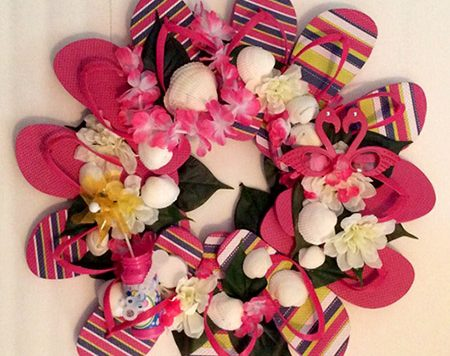 One of our favorite flip flop crafts is the flip flop wreath, and now that summer stuff is back on the shelves it's the perfect time to make one! Here is my version of the flip flop wreath, embellished with fake flowers and some other summery items.