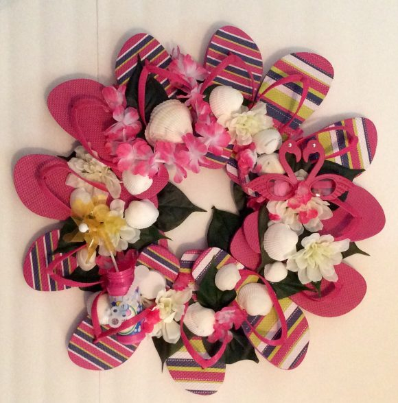 Flip Flop Wreath Tutorial - One of our favorite flip flop crafts is the flip flop wreath, and now that summer stuff is back on the shelves it's the perfect time to make one!  Here is my version of the flip flop wreath, embellished with fake flowers and some other summery items.